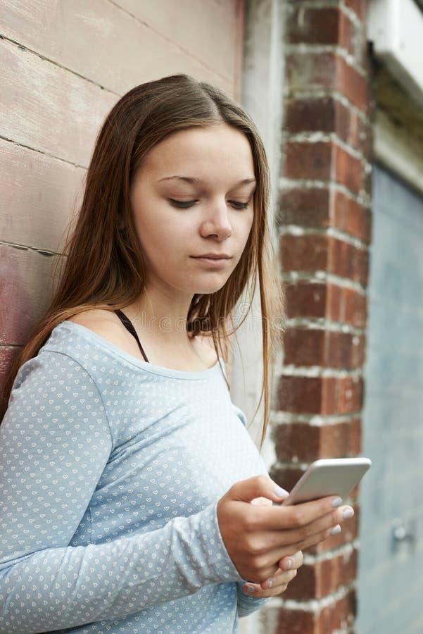 Adolescente che manda un sms sul telefono cellulare nell'ambiente urbano fotografia stock libera da diritti