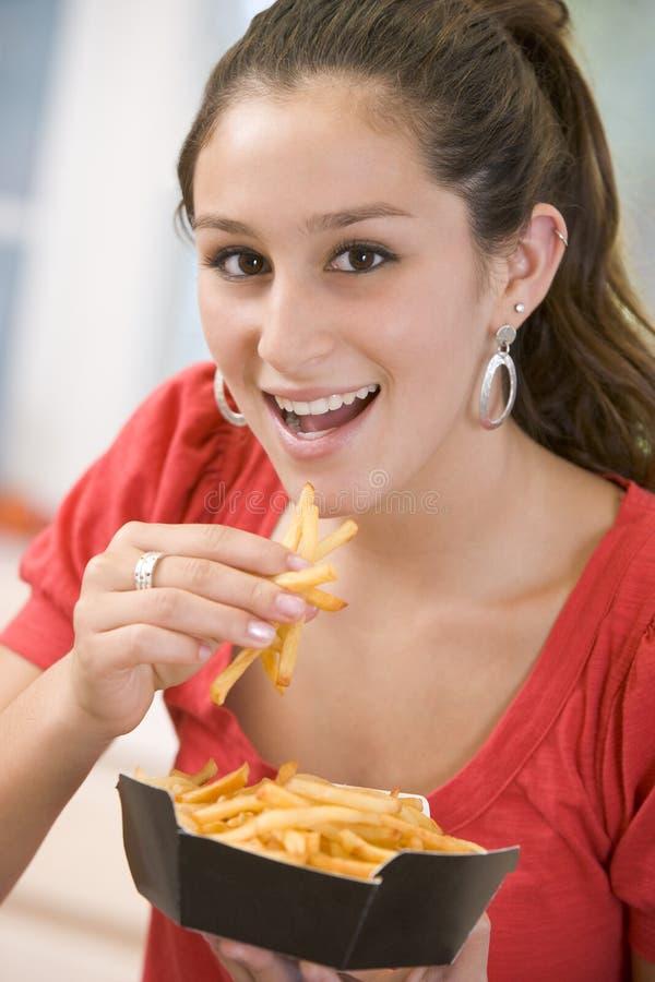Adolescente che mangia le patate fritte immagine stock