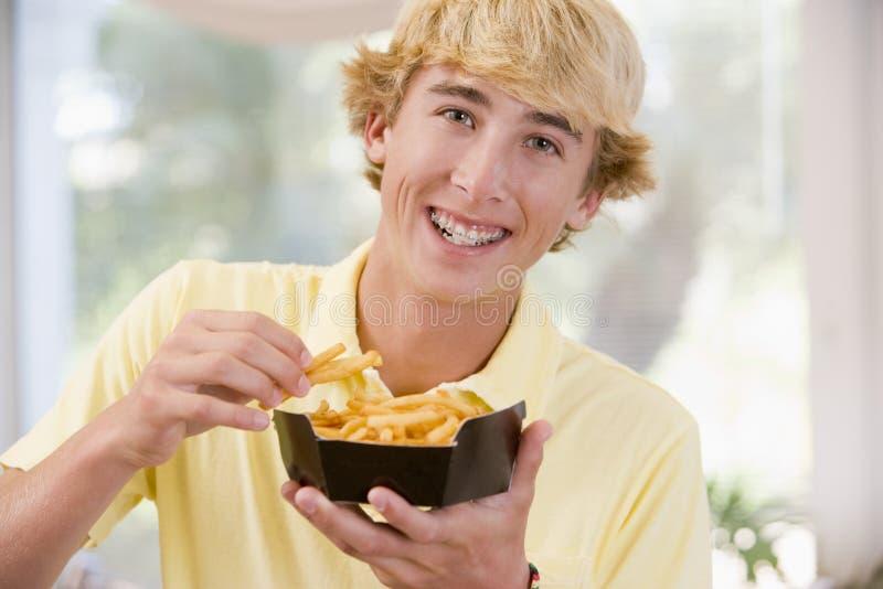 Adolescente che mangia le patate fritte fotografie stock