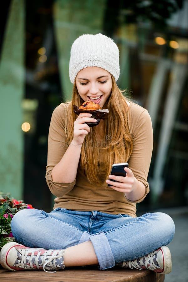 Adolescente che mangia muffin che guarda in telefono fotografia stock