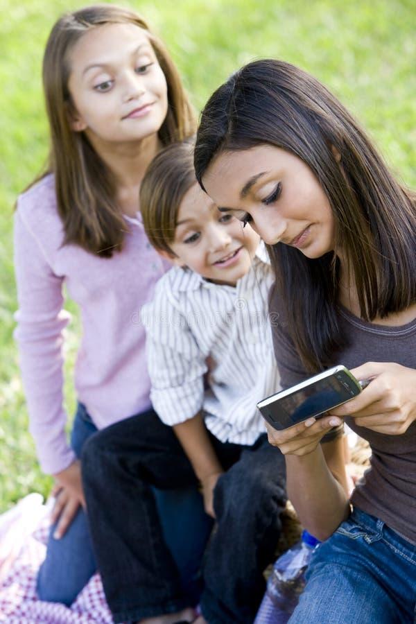 Adolescente che mostra telefono mobile ai fratelli germani fotografia stock libera da diritti