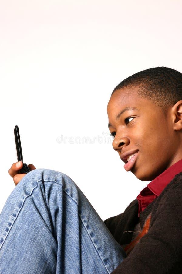 Adolescente che per mezzo del telefono delle cellule immagini stock