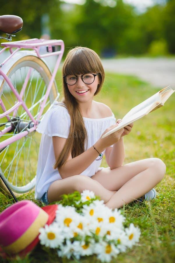 Adolescente che posa con la bicicletta su fondo del giardino immagini stock