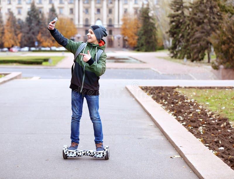 Adolescente che prende selfie mentre guidando sul gyroscooter immagini stock libere da diritti