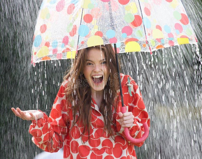 Adolescente che ripara dalla pioggia sotto l'ombrello immagini stock