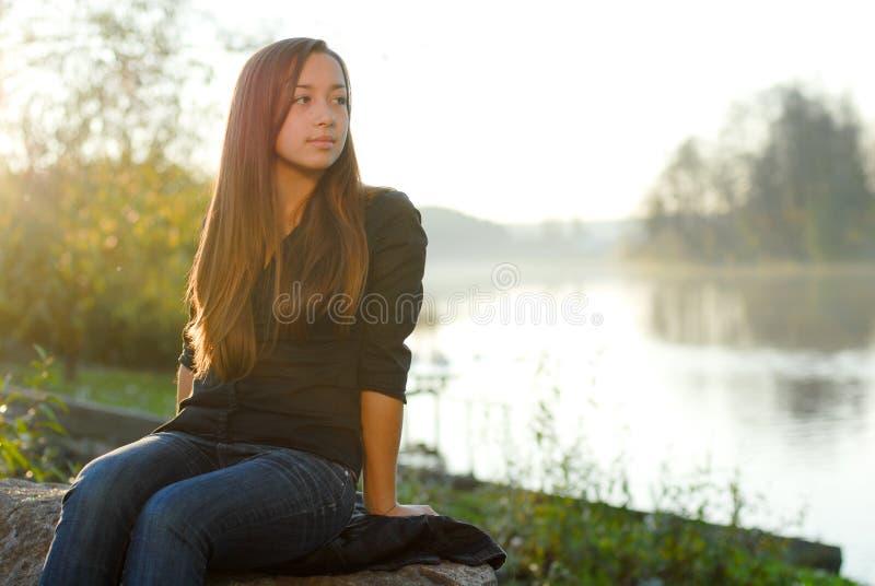 Adolescente che riposa dal fiume all'ora dorata immagine stock libera da diritti
