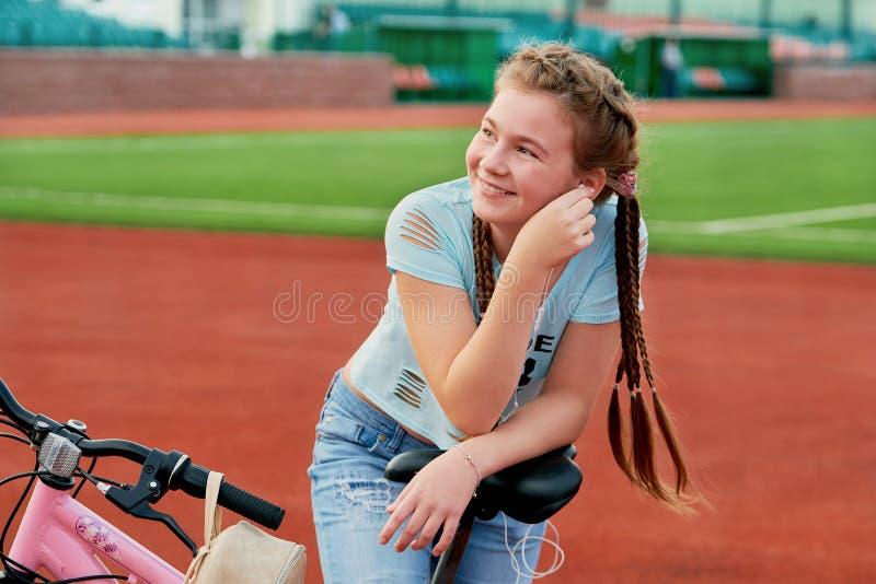 Adolescente che si rilassa su uno stadio Ragazza che si rilassa su un tempo libero della bici fotografia stock libera da diritti