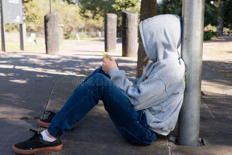 Adolescente che si siede con lo Smart Phone immagine stock libera da diritti