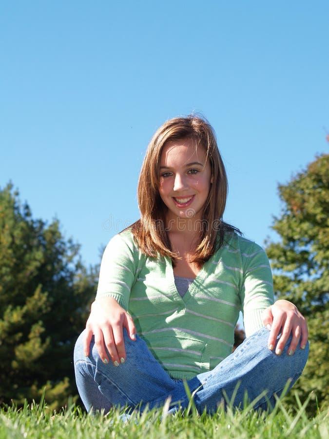 Adolescente che si siede nell'erba fotografia stock libera da diritti