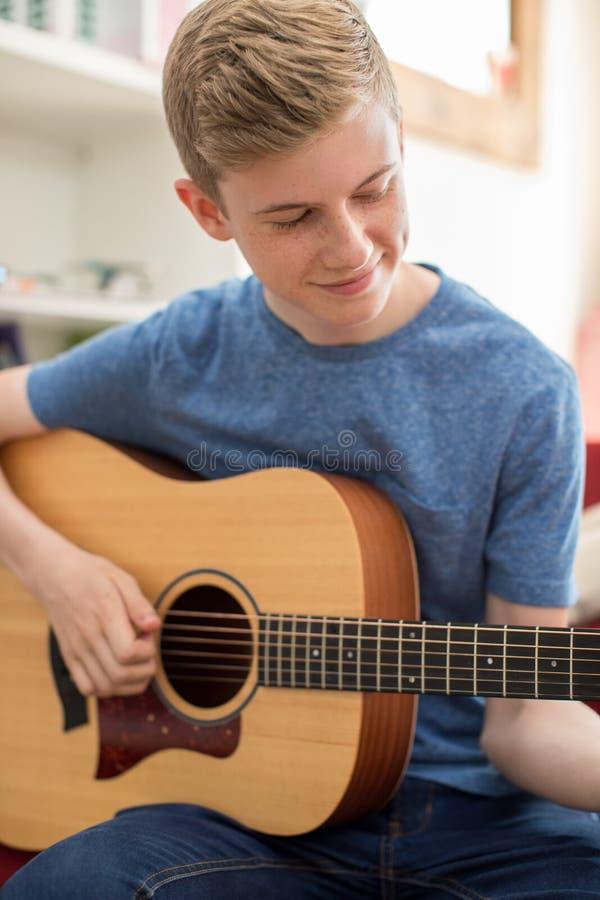 Adolescente che si siede su Sofa At Home Playing Guitar fotografia stock libera da diritti