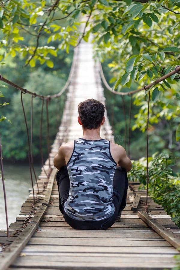 Adolescente che si siede su un ponte fotografia stock