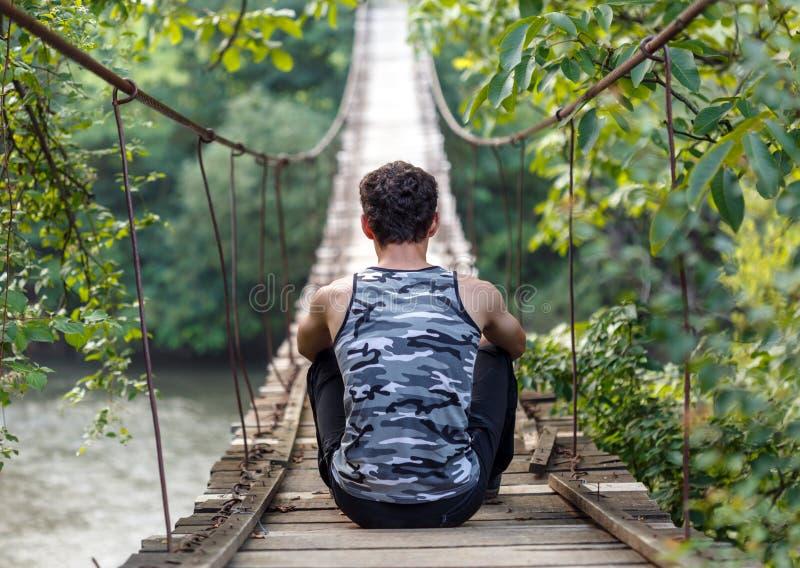 Adolescente che si siede su un ponte immagine stock libera da diritti