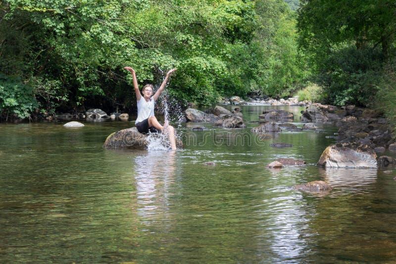 Adolescente che si siede su una roccia, spruzzante acqua e divertentesi i fotografia stock
