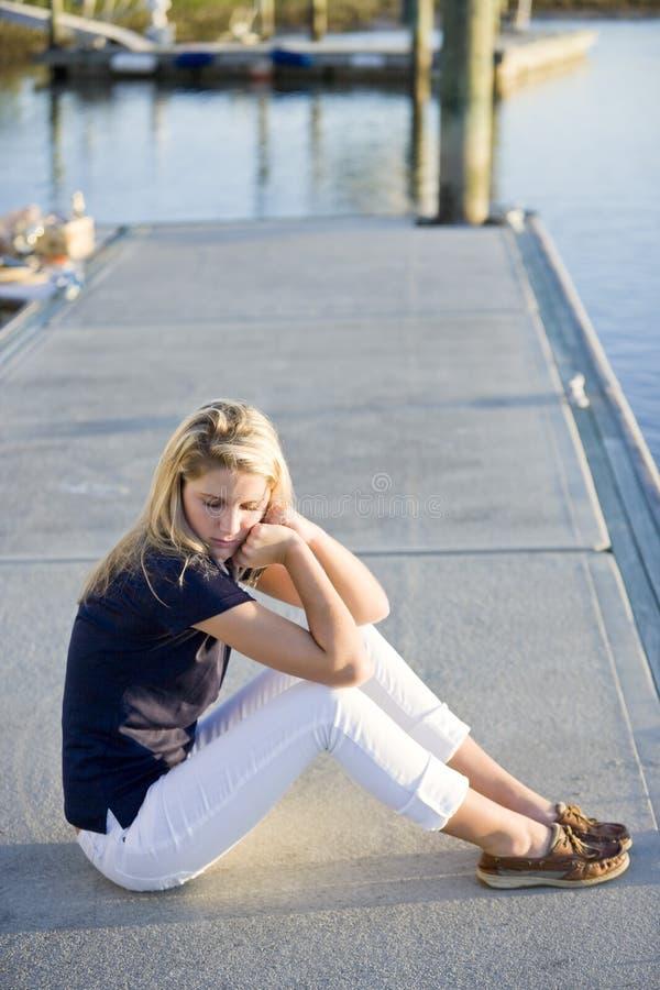 Adolescente che si siede sul bacino dall'acqua fotografie stock libere da diritti