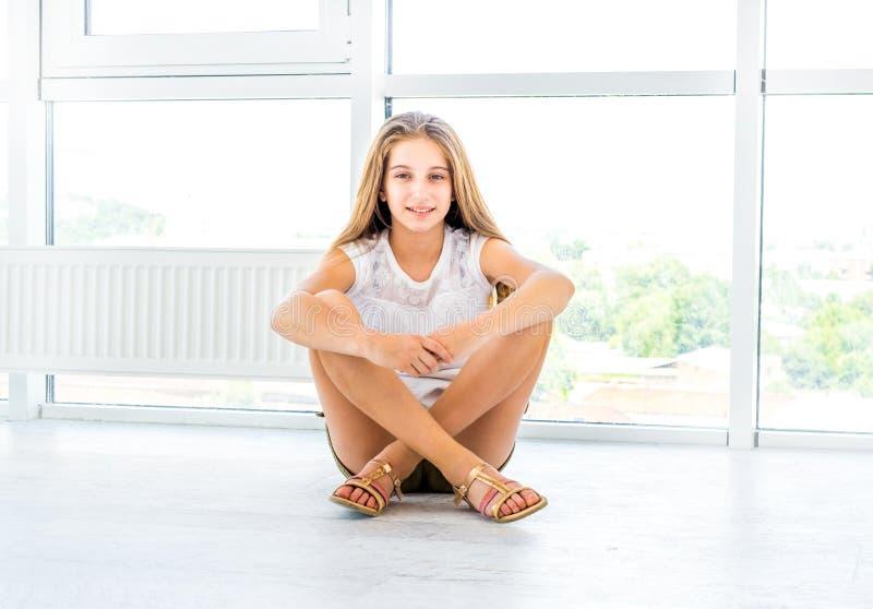 Adolescente che si siede sul pavimento nella stanza bianca fotografie stock libere da diritti