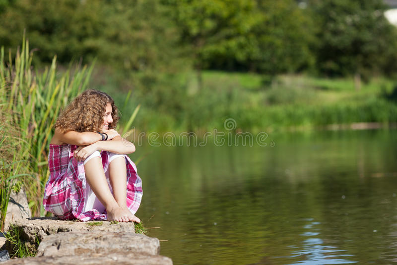 Adolescente che si siede sulla roccia mentre distogliendo lo sguardo dal lago fotografia stock libera da diritti