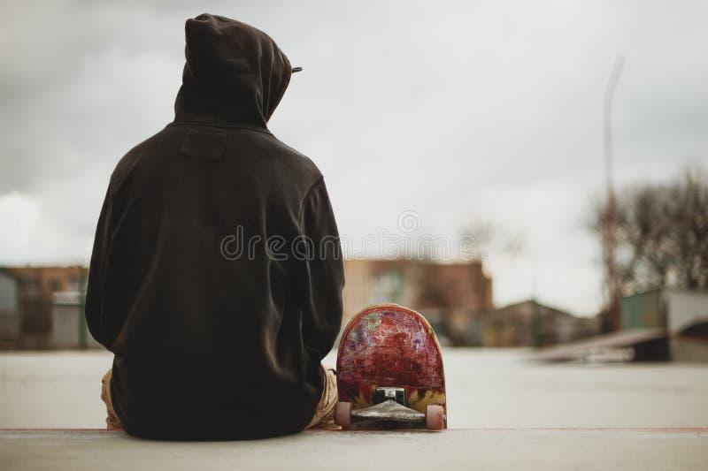 Adolescente che si siede in una maglietta felpata nera che giudica un pattino su un fondo dei bassifondi urbano fotografia stock