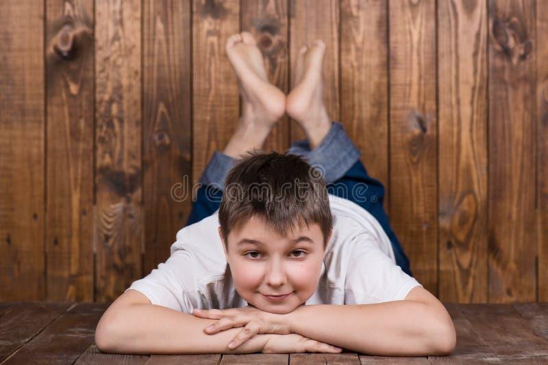 Adolescente che si trova sul suo stomaco Contro lo sfondo delle plance di legno fotografia stock