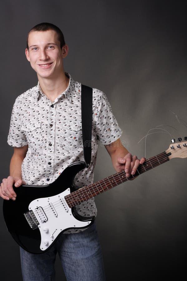 Adolescente che tiene la chitarra fotografia stock