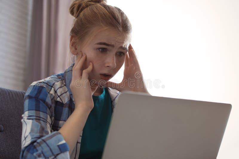 Adolescente chocado com portátil Perigo do Internet imagens de stock royalty free