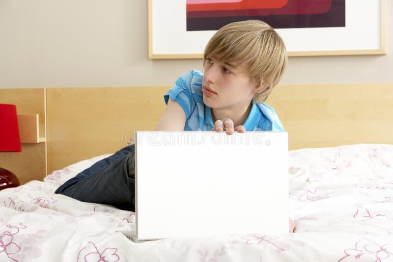 Adolescente colpevole che utilizza computer portatile nella camera da letto fotografia stock libera da diritti