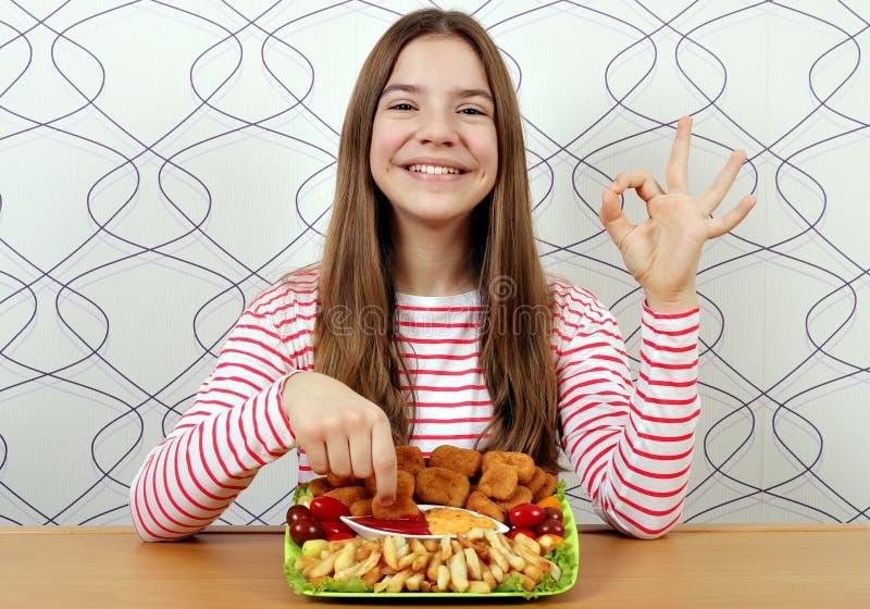 Adolescente com as pepitas de galinha saborosos e o sinal da m?o da aprova??o fotos de stock