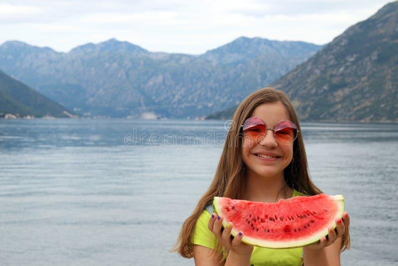 Adolescente com melancia em uma baía Montenegro de Kotor das férias de verão imagem de stock