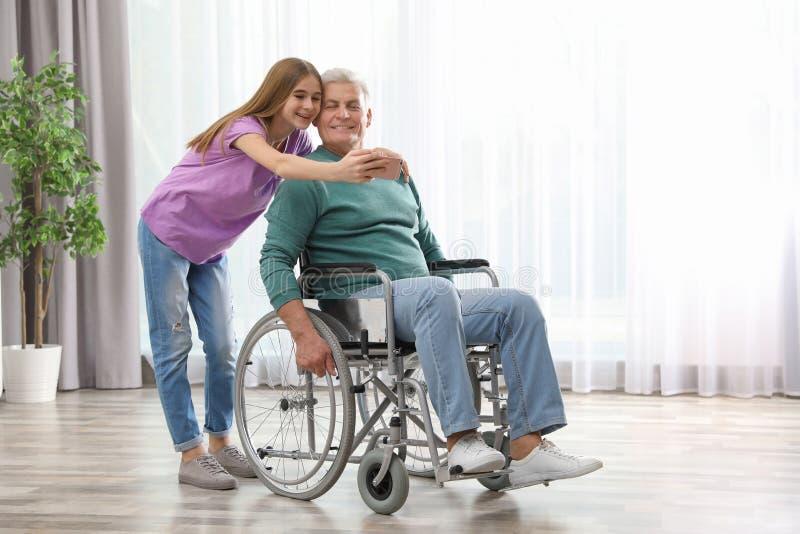 Adolescente com o avô na cadeira de rodas que toma o selfie imagem de stock royalty free