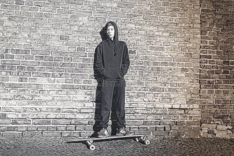 Adolescente com o hoodie que está em uma placa longa fotografia de stock