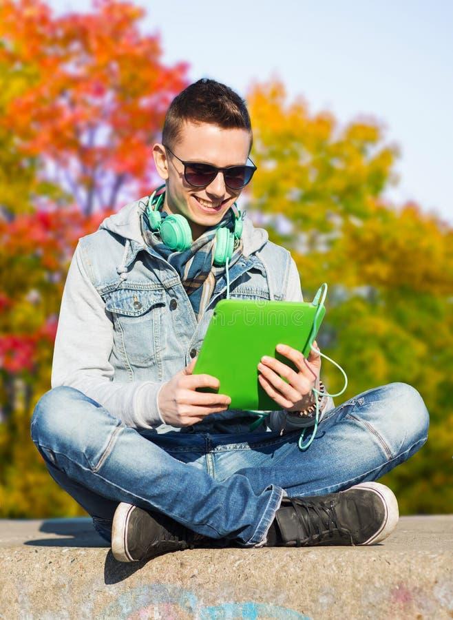 Adolescente com PC e fones de ouvido da tabuleta imagem de stock royalty free