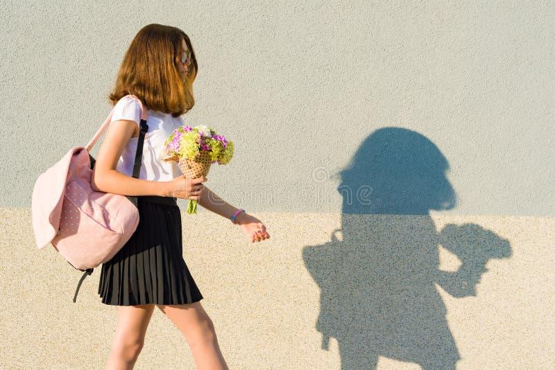 Adolescente com ramalhete, trouxa Vai contra a parede cinzenta, espaço da cópia foto de stock royalty free