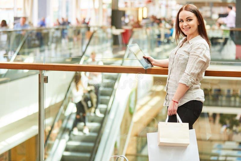 Adolescente com sacos de compras e PC da tabuleta imagens de stock royalty free