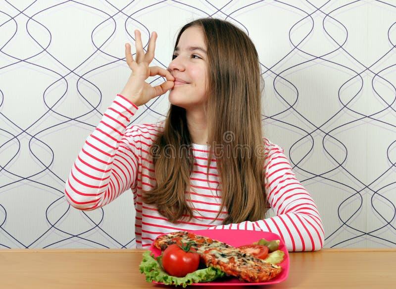 Adolescente com sinal saboroso do sandu?che e da m?o da aprova??o foto de stock