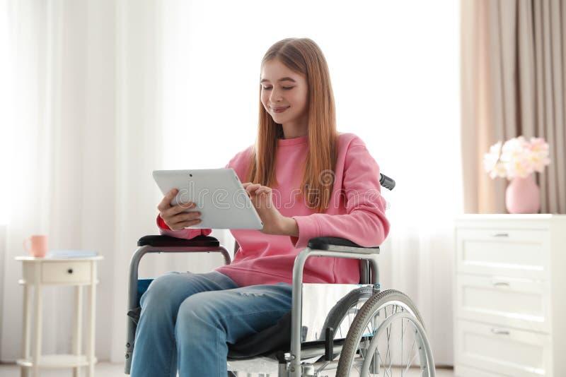 Adolescente com a tabuleta na cadeira de rodas fotografia de stock royalty free
