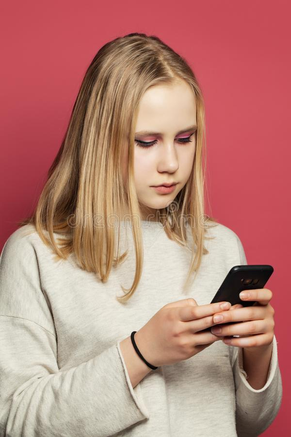 Adolescente com texting do telefone celular Menina do adolescente com retrato do smartphone fotografia de stock royalty free