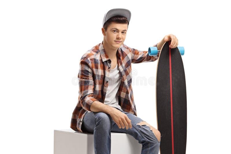 Adolescente com um assento do longboard fotos de stock