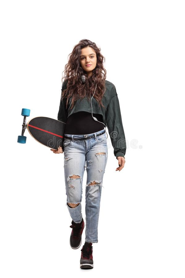 Adolescente com um longboard que anda para a câmera foto de stock