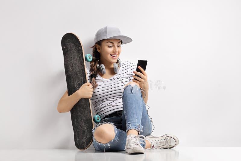 Adolescente com um skate usando um telefone imagens de stock