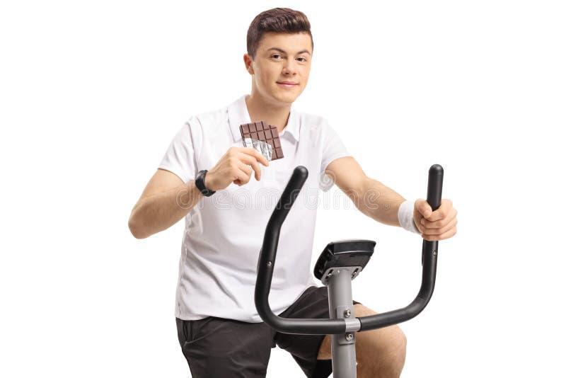 Adolescente com uma barra de chocolate que exercita em uma bicicleta estacionária fotografia de stock royalty free