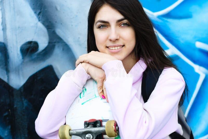 Adolescente com uma placa do patim ao ar livre foto de stock