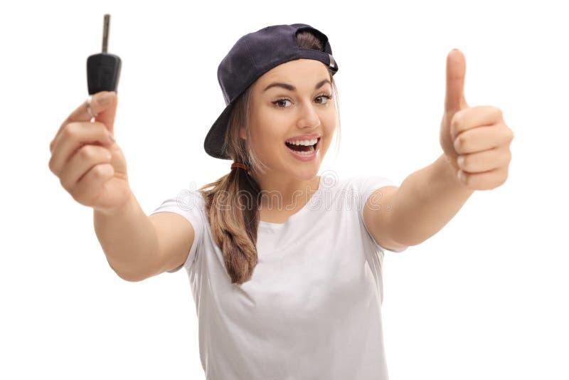 Adolescente comblée tenant la clé et le pouce de voiture  image stock
