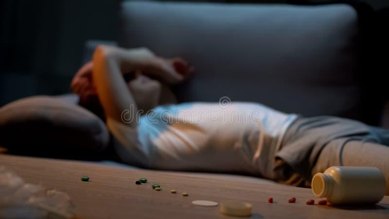 Adolescente comprimido que encontra-se no sofá, overdose da medicamentação, pilha dos analgésicos na tabela imagem de stock