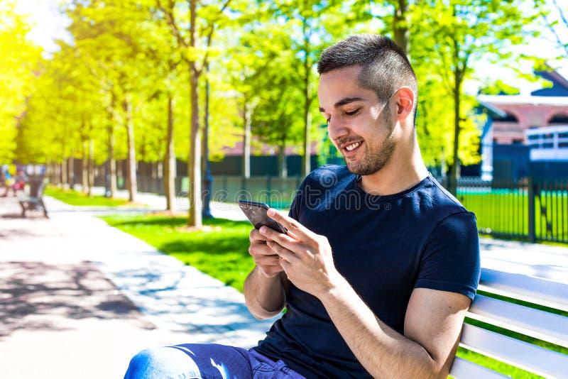 Adolescente con buen humor usando los apps en smartphone imagen de archivo
