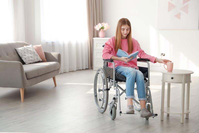 Adolescente con el libro y bebida en silla de ruedas fotografía de archivo libre de regalías