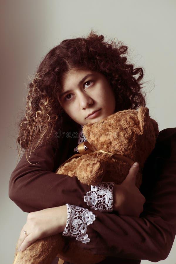 Adolescente con el pelo rizado y uniforme escolar de estilo retro con un viejo oso de peluche en los brazos, con cara pensativa imagen de archivo