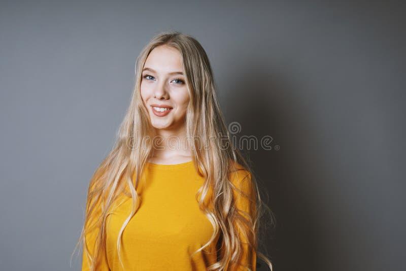 Adolescente con el pelo rubio muy largo y la sonrisa de emisión imagen de archivo