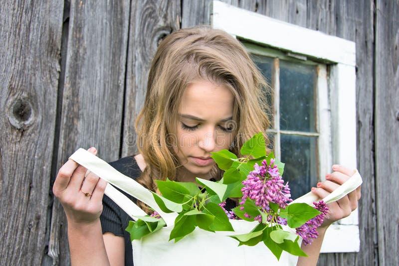 Adolescente con el ramo de la lila en bolso foto de archivo libre de regalías