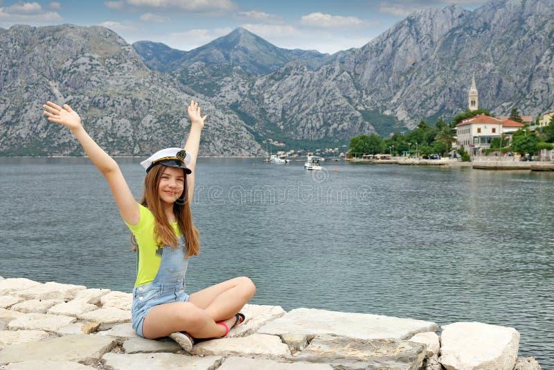 Adolescente con el sombrero y las manos del marinero para arriba en vacati del verano fotos de archivo