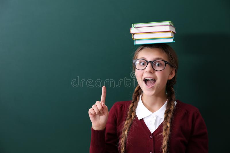 Adolescente con i libri su lei lavagna verde vicina diritta capa della scuola immagine stock