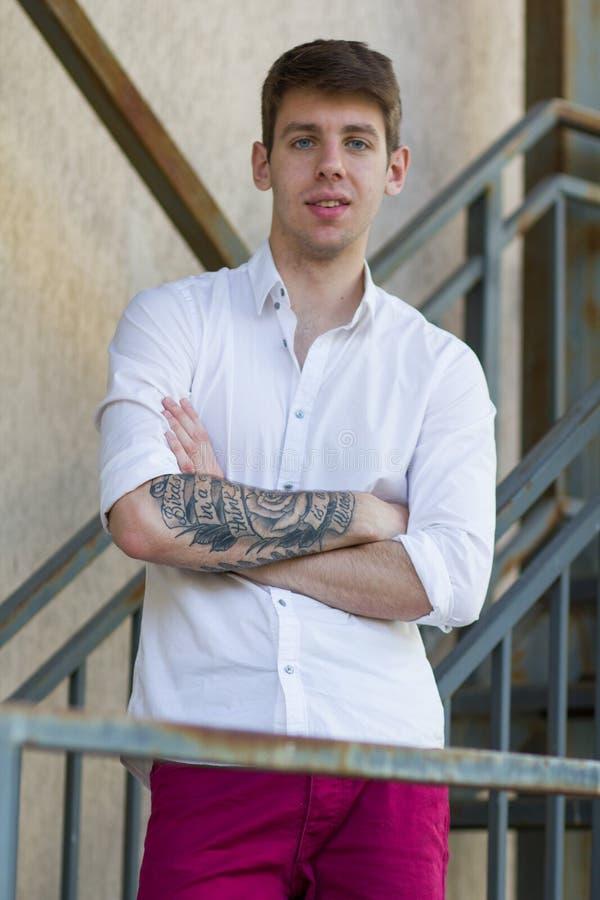 Adolescente con il braccio tatuato che esamina macchina fotografica immagini stock